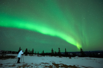 Man photographing the Aurora Borealis in Alaska