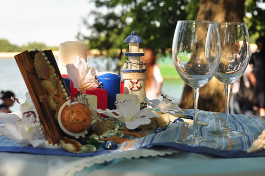 Glasses are on the festive table in the style of the wedding in the marine theme.
