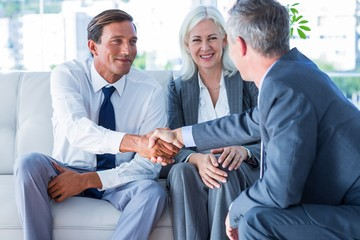 Business people shake hands on couch