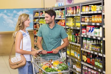 Smiling bright couple buying food products