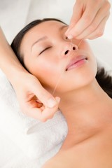 Hands threading beautiful womans face