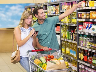 Smiling bright couple buying food products showing shelf