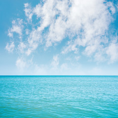 blue sea and white clouds in sky over it
