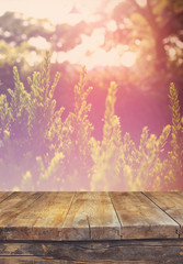 vintage wooden board table in front of dreamy abstract landscape
