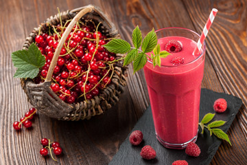 Raspberry smoothie and red currant in basket