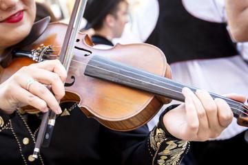 Músico tocando el violín en la calle. Violinista dando recital en el exterior. Primeros planos de un violín. Mariachi amenizando evento.