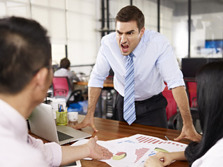 Angry boss yelling at business meeting