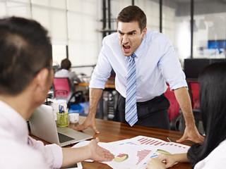 caucasian boss yelling at asian subordinates during business meeting