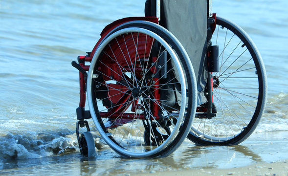 wheelchair-red by the sea on sandy beach in summer