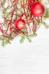 two red Xmas balls and tree branch on blank paper