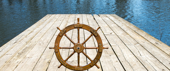 Old boat steering wheel  on wooden board. Composite image, useful for different ideas of leadership