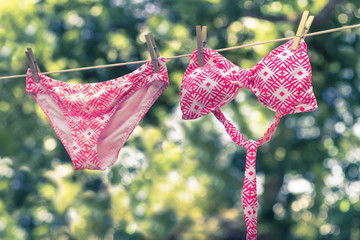 Adorable woman's bikini bathing suiting hanging on clothesline on a summer day.