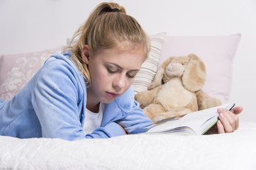 Teenage girl reading on a bed