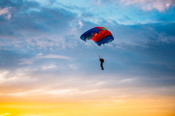 Zelfklevend Fotobehang Luchtsport Skydiver On Colorful Parachute In Sunny Sky