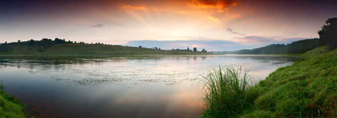 Foto op Aluminium Rivier Fantastic foggy river with fresh green grass in the sunlight. Sun beams through tree. Dramatic colorful scenery, Russia. Beauty world.