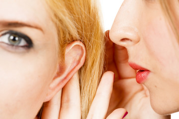 Close-up of one woman whispering to another woman as if telling a secret or confidential information. The focus is on the model's mouth.