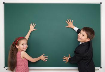 boy and girl write on school board
