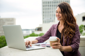 Attractive female at coffee shop on her computer working freelance independent social networking