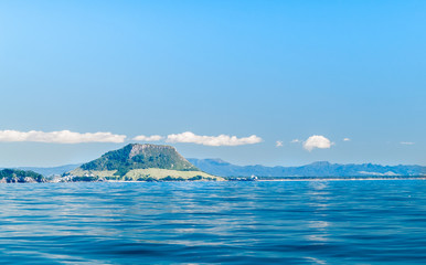 Strip white could parallel with horizon and over Mount Maunganui landmark across calm blue ocean