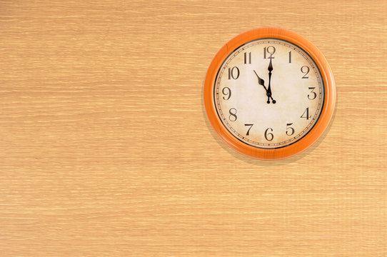 Clock showing 11 o'clock on a wooden wall