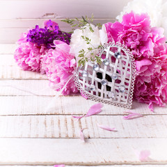 Decorative white heart and fresh pink and white peonies