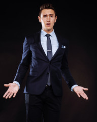 young pretty business man standing on black background