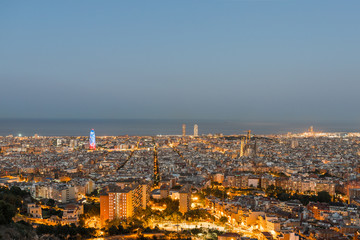Top view and night photography from an illuminated Barcelona. The panorama shows the famous Sagrada Familia, the illuminated Torre Agbar and the Towers of the Port Olimpic until the harbor