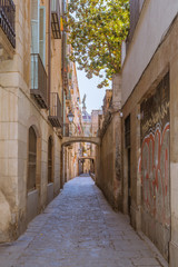 Narrow streets and alleys in the Ciutat Vella, the historic part of Barcelona. The lane leads to the church Basilica of Our Lady of Mercy, Basílica de la Merce
