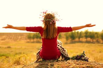 Beautiful girl sitting on haystack in field