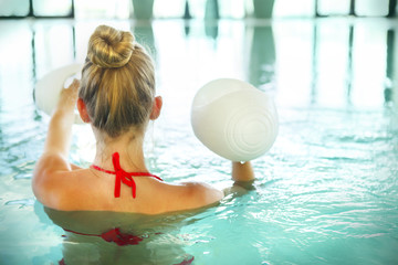 Blond young woman doing aqua aerobics with dumbbells in swimming
