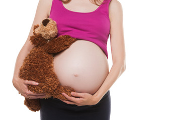 Close up on pregnant belly with toy. Woman expecting a baby