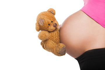 Close up of pregnant belly with toy. Woman expecting a baby
