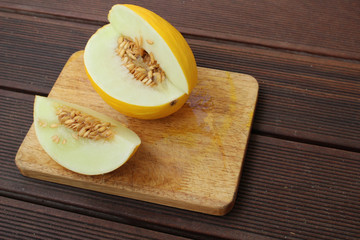 Yellow melon on a wooden cutting board