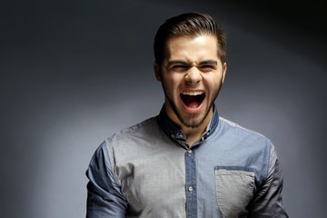 Portrait of shouting man in blue shirt on gray background