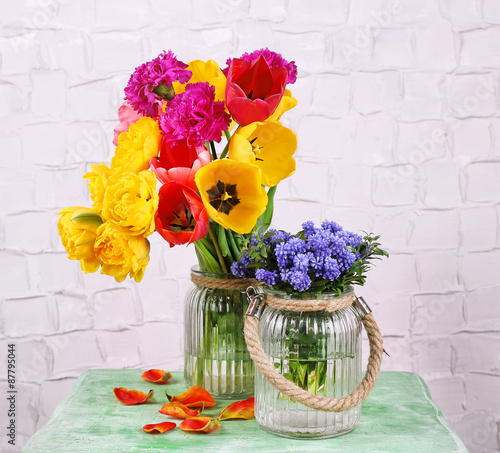 Beautiful Flowers In Vases On Wall Background Stock Photo And
