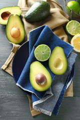 Sliced avocado and lemon lime on wooden background