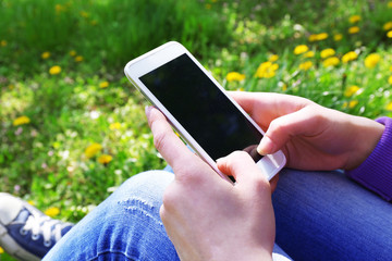 Young woman with mobile phone sitting on green grass outdoors
