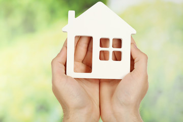 Female hands holding house on green blurred background