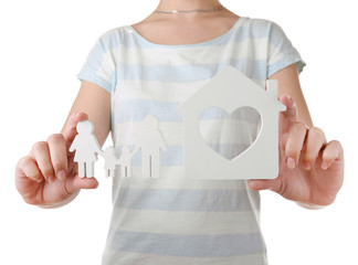 Female hands with small model of house and family isolated on white