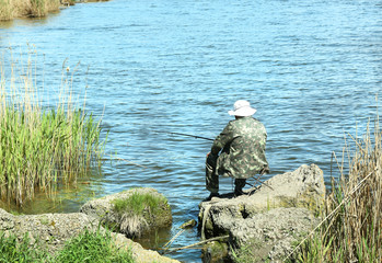 Man fishing on riverbank