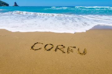 Corfu written on golden  beach, Agios Gordis, Corfu, Greece. Selective focus.