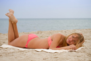 Young beautiful girl in bikini sunbathing on the beach; freedom summertime concept