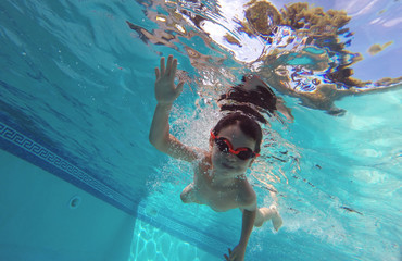 Boy smiles, swimming under water in the pool