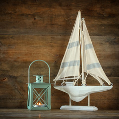old vintage wooden white sailing boat and lantern on wooden table