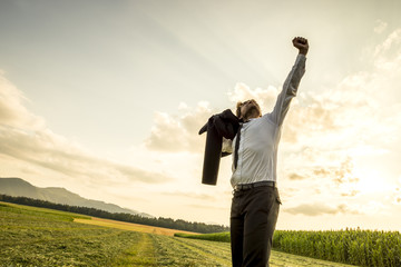 Thankful Man in the Field Raising Arm for Success