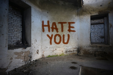 text hate you on the dirty old wall in an abandoned ruined house