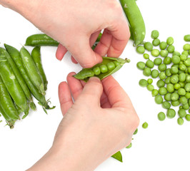 Process of manual cleaning of green peas on white background
