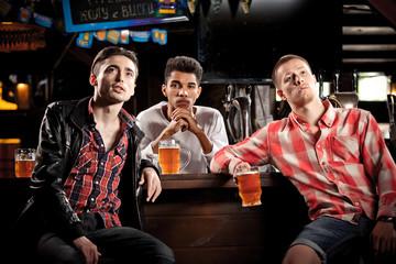 Watching TV in bar. men drinking beer sitting  bar