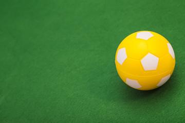 Yellow Soccer ball on green field