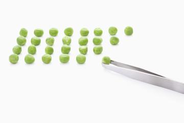 Grüne Erbsen mit Pinzette auf weißem Hintergrund